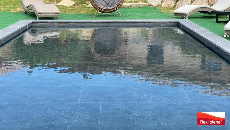 Feuille de pierre en piscine - Vue d'une piscine dans le Sud de la France avec le fond mobile de piscine relevé pour affleurer l'eau.<br>Feuilles de pierre Noir Stellaire