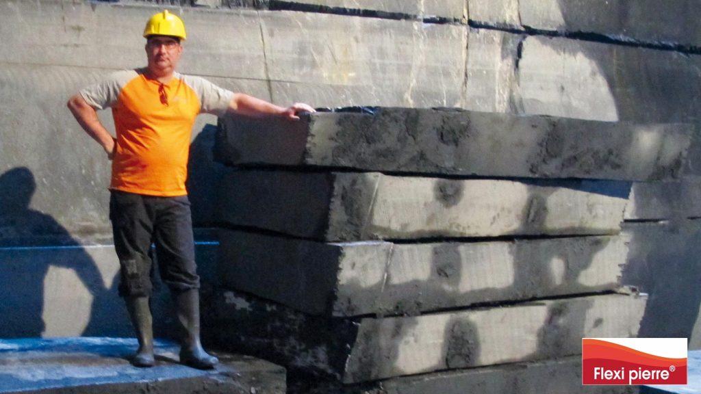 Photo en fond de carrière, en équipement de sécurité, sur des blocs d'ardoise fraîchement extraits.  Ils vont être transformés en feuilles de pierre.