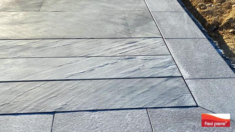 Piscine à fond mobile recouvert de feuille de pierre Noir Stellaire, fond et marches en positions hautes.